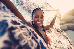 Woman on beach with scarf in the breeze. Beautiful woman with cloth in the breeze of a summer day. African young female on beach with a scarf looking at camera royalty free stock photos
