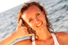 Woman on the beach shows Royalty Free Stock Photography