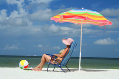 Woman on the beach sittin on a chair Stock Images