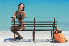 Woman by the beach sitting on bench. Young woman sitting on bench by the beach with bag and mat Royalty Free Stock Photo