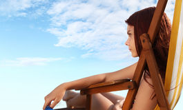 Woman at the beach sitting on deckchairs Royalty Free Stock Image