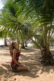 Woman on the beach sitting palm tree Stock Photography
