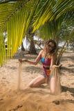 Woman on the beach sitting palm tree Stock Photo