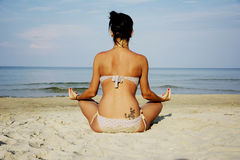 Woman on beach sitting relaxed Stock Photo