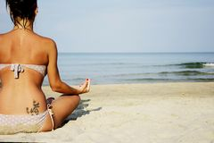Woman on beach sitting relaxed. Good looking woman on beach sitting on her legs enjoying sun on her back.She is wearing bikini with white dots.She is feeling royalty free stock images