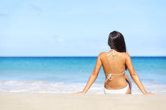 Woman on beach sitting in sand looking at ocean. Enjoying sun and summer travel holidays vacation getaway. Girl in bikini relaxing under blue sky stock photo