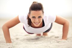 Woman on the Beach Smiling While Doing Push Up. Happy fitness caucasian woman on the beach smiling while doing push up exercise. Active and healthy lifestyle royalty free stock images
