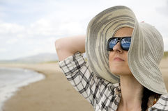 Woman on beach with sun hat Stock Photos