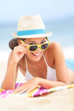 Woman on beach with sunglasses. Looking flirting at camera smiling happy and joyful during summer vacations holiday travel. Beautiful young multiethnic Asian Stock Photos