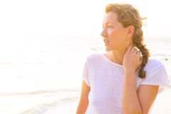Woman on beach at sunrise. Young woman on beach at sunrise Royalty Free Stock Image