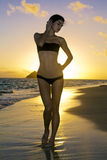 Woman on the beach at sunrise Stock Photo
