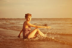 Woman on the beach at sunset. Stock Photo