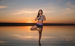 Yoga woman on the beach at sunset. Stock Photography