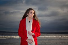 Woman on beach at sunset. A woman wearing a red coat standing on a beach at sunset Royalty Free Stock Images