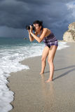 Woman on beach taking photo Royalty Free Stock Photography