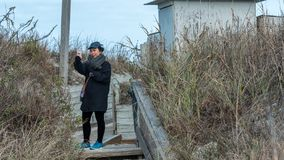 Woman on beach taking selfie on a path in the grass. Woman on beach at Emerald Isle NC taking selfie wearing black clothes and blue sneakers royalty free stock photos