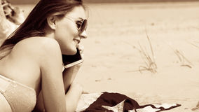 Woman on beach talking by mobile phone. Royalty Free Stock Image