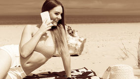 Woman on beach talking by mobile phone. Royalty Free Stock Photo