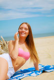 Woman on beach talking by mobile phone. Royalty Free Stock Images