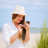 Woman on beach texting on smartphone. Communication concept. Young woman spending time on summer beach texting messages on smartphone. Girl using mobile phone Stock Photography