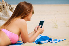 Woman on beach texting on smartphone. Stock Images