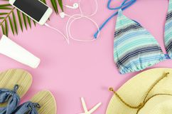 Woman beach things top view. Hat, bikini, smartphone and slippers. Flat lay frame royalty free stock image
