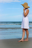 Woman On Beach Touching Hat And Looking At Ocean. Woman in white dress standing on beach touching straw hat and looking at ocean Royalty Free Stock Photos