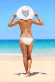 Woman on beach travel vacation lifestyle concept. Bikini girl looking at ocean sea view wearing sun hat on holidays under blue clear summer sky on tropical royalty free stock photography