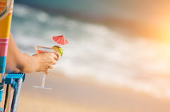 Woman on Beach with Tropical Drink. Woman Relaxing on Beach with Tropical Drink royalty free stock image