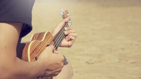 Woman on beach with ukulele Stock Photography