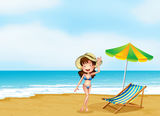A woman at the beach with an umbrella and a chair Royalty Free Stock Image