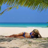 Woman at beach under palm tree Stock Photos