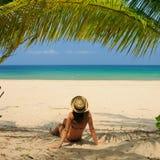 Woman at beach under palm tree Stock Photos