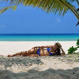 Woman at beach under palm tree Royalty Free Stock Photos