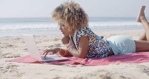 Woman On The Beach Using A Computer Stock Images