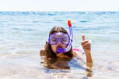 Woman on beach vacation holidays with snorkel lying in sea with snorkeling mask smiling happy enjoying the sun on sunny summer day Stock Image