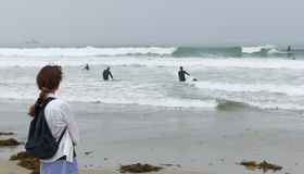 A Woman on a Beach Watches Surfers Stock Photo