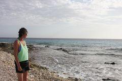 Woman on a beach watching the ocean. Woman admiring the Ocean from a beach stock photography