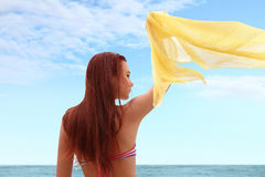 Woman at the beach waving a scarf Stock Photography