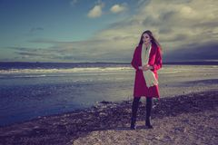Woman on beach. A woman wearing a long red coat standing on the beach at sunset Stock Photo