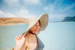 Woman at beach, wearing straw hat and swim wear. Sunny day in the waves of greece. Wide angle shot. Smiling woman at beach, wearing straw hat and swim wear royalty free stock image