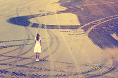 Woman on beach. Woman in white dress stand on an empty sand beach with wheel trace curves. Vintage filter effect used Stock Photography