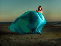 Woman on beach wind blowing blue dress Royalty Free Stock Photography