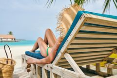 Woman at beach on wooden sun bed loungers. Young woman at beach on wooden sun bed loungers. Summer vacation at Maldives stock photo