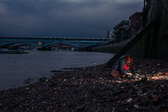 Woman beachcombing in city at night Stock Photo