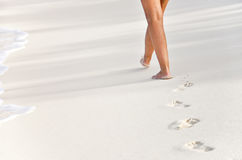 Woman beachwalk with footprints Stock Photos