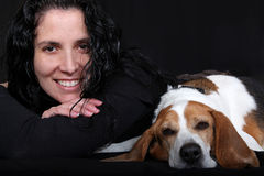 Woman with Beagle Dog. A portrait of a pretty middle-aged woman with her pet Beagle dog, on black background Royalty Free Stock Images