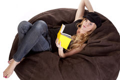Woman on bean bag reading. A woman in laying on a bean bag with a book royalty free stock photography