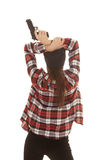 Woman in beanie and plaid shirt back gun Royalty Free Stock Image