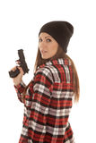 Woman in beanie and plaid shirt gun look over shoulder Royalty Free Stock Photos